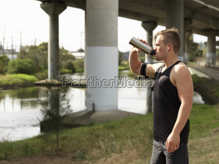 young man beside river drinking from