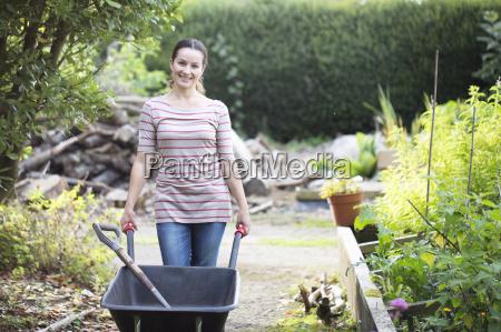 portrait of female gardener pushing wheelbarrow