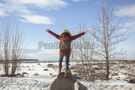 woman standing on rock with arms