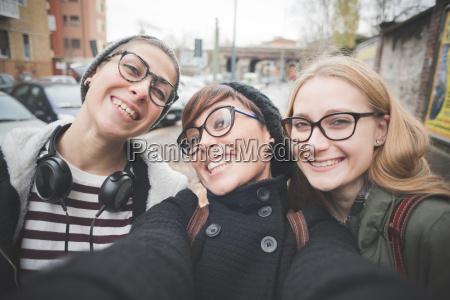 three sisters taking selfie on street