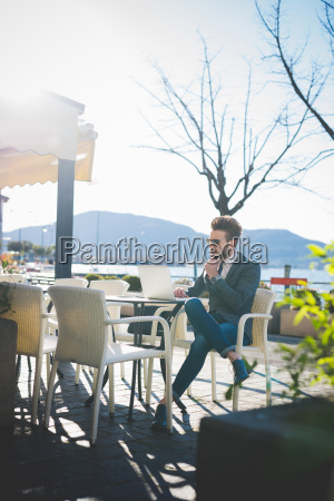businessman using laptop at lakeside cafe