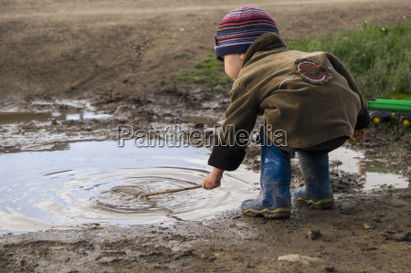 male toddler wearing rubber boots playing
