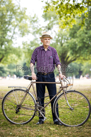 senior man with bicycle in park