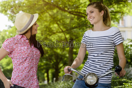 young woman on bicycle talking to