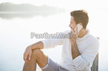 young man chatting on smartphone whilst