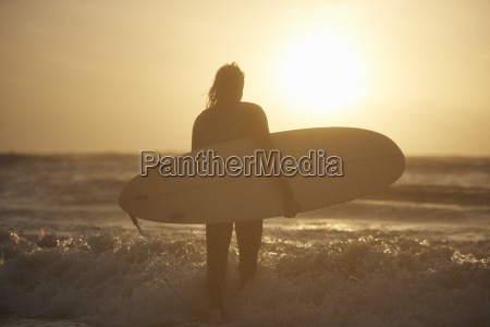 silhouette of young male surfer carrying