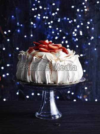 strawberry covered pavlova on glass cake