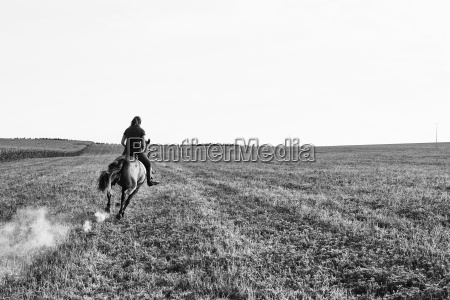 bw image of woman riding galloping
