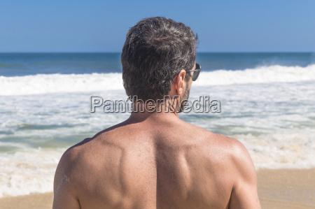 mature man looking at ocean rear