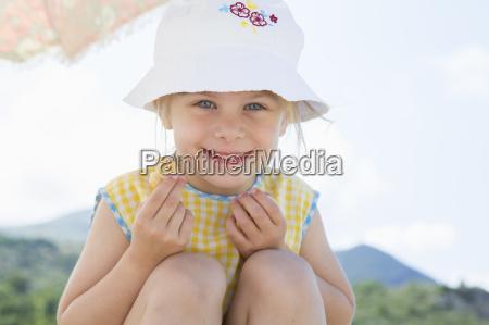 girl wearing sunhat eating doughnut