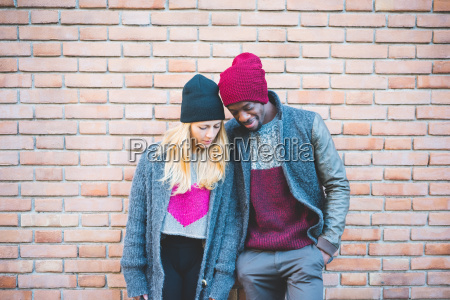 couple enjoying quiet moment against brick