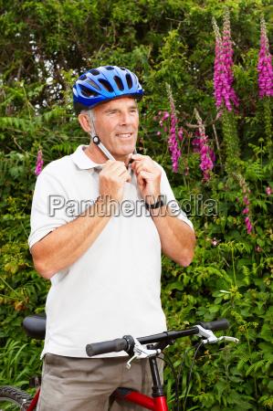 senior man fastening cycle helmet