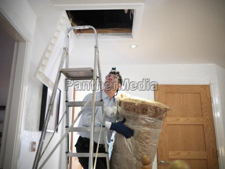 man preparing to insulate loft in