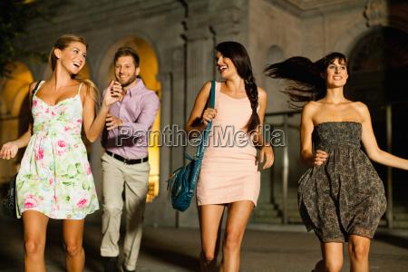 friends walking on city street at