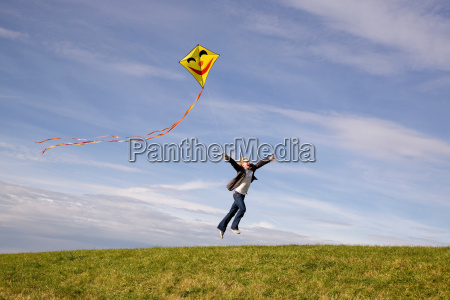 man jumping flying a kite