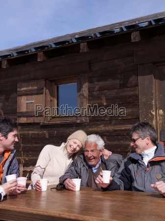 4 people laughing holding cups