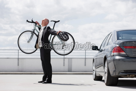 man carrying bycicle stretching near car