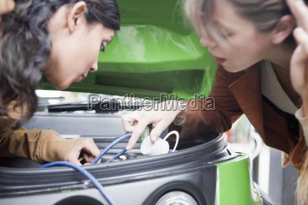 women plugging in electric car