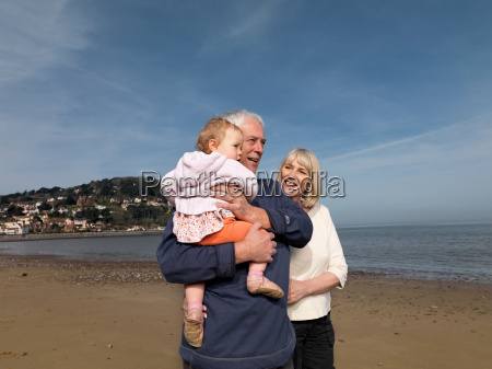 mature couple with baby on beach