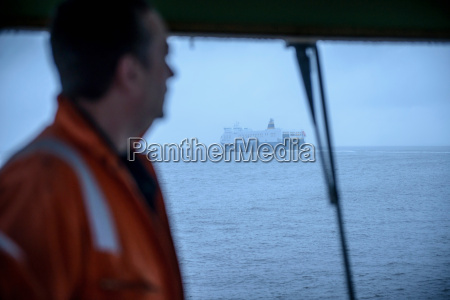 sailor on tug looking through window