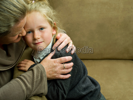 a young girl being hugged by