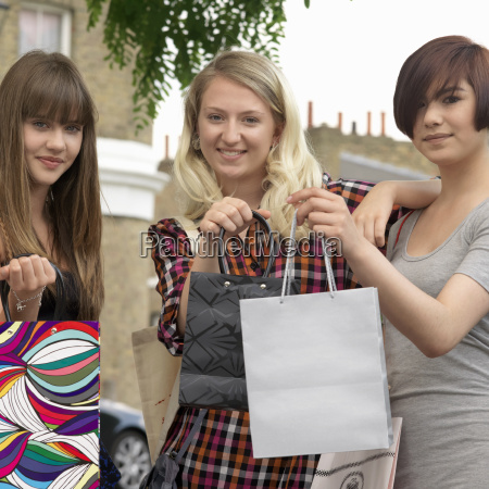3 young women holding up bags