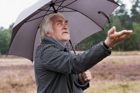 senior man under umbrella checking for