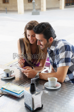 couple sharing postcard in cafe
