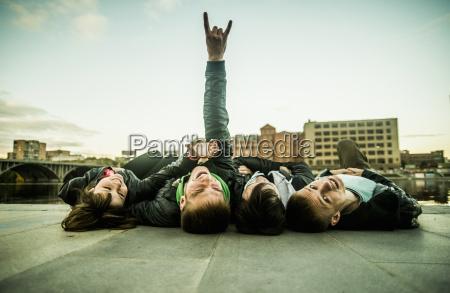 four friends lying on backs one