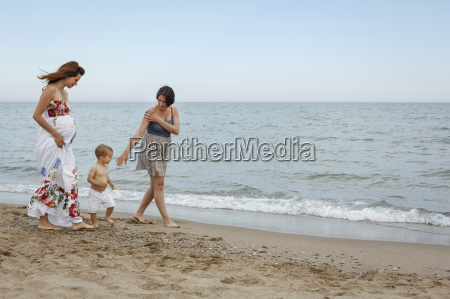 women and toddler walking along shore