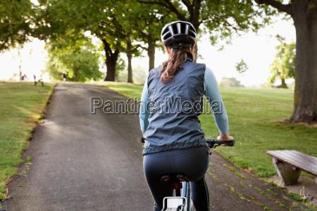 woman cycling uphill at park
