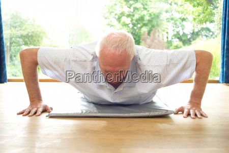 older man doing pushups indoors