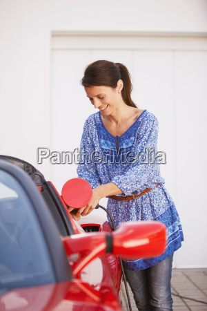 woman plugging in her electric car