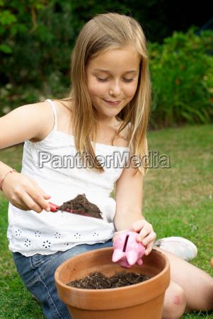 young girl planting a piggy bank