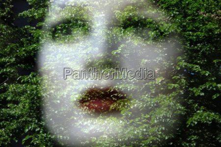 womans face reflected in window