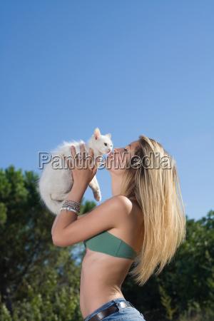 teen girl kisses kitten outside