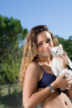 young woman holds white kitten outside