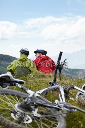mountain bikers relaxing on hillside