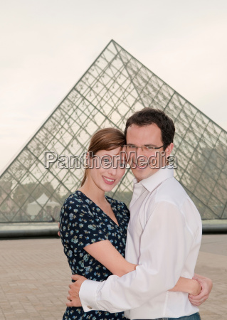 happy couple embrace at the louvre