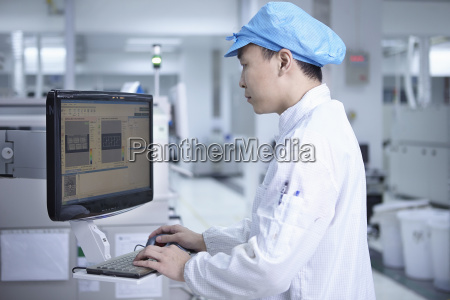 worker using computer in factory that