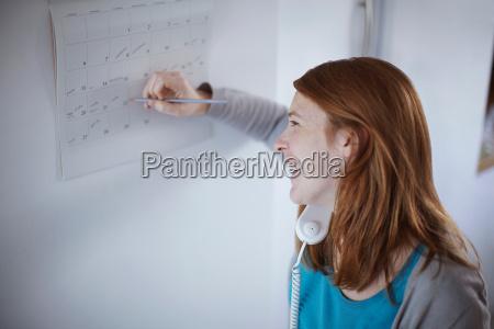 girl on telephone writing on calendar