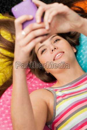 woman lying and checking her phone