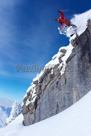 skier jumping on rocky slope
