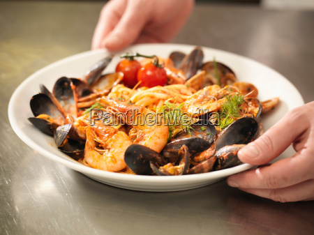 chef serving bowl of prawns and
