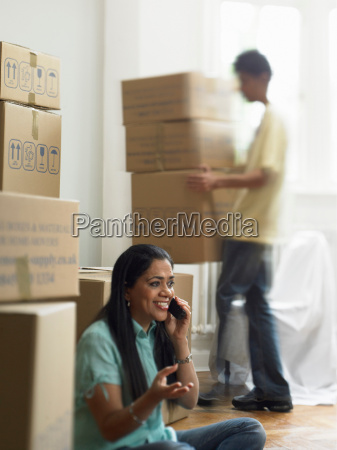 woman on phone and unpacking boxes