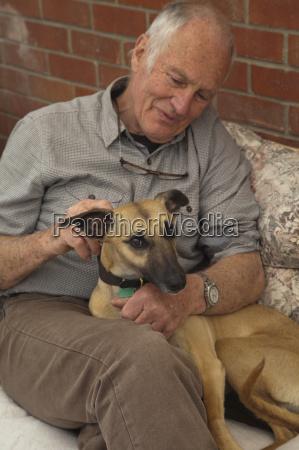 senior man sitting stroking pet dog