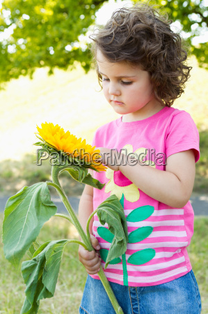 girl examining wildflower outdoors