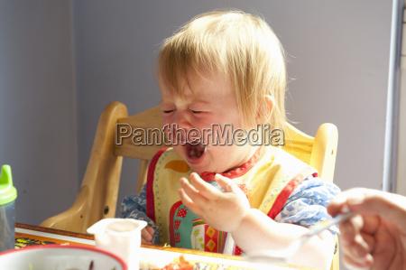 toddler girl crying at table