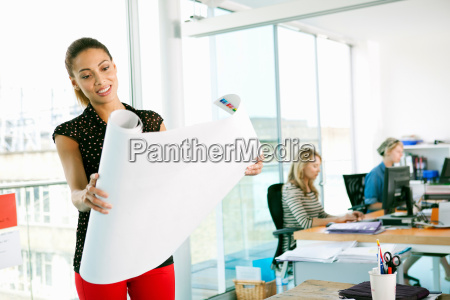 businesswoman unrolling blueprint