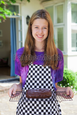 girl holding cake on cooling tray